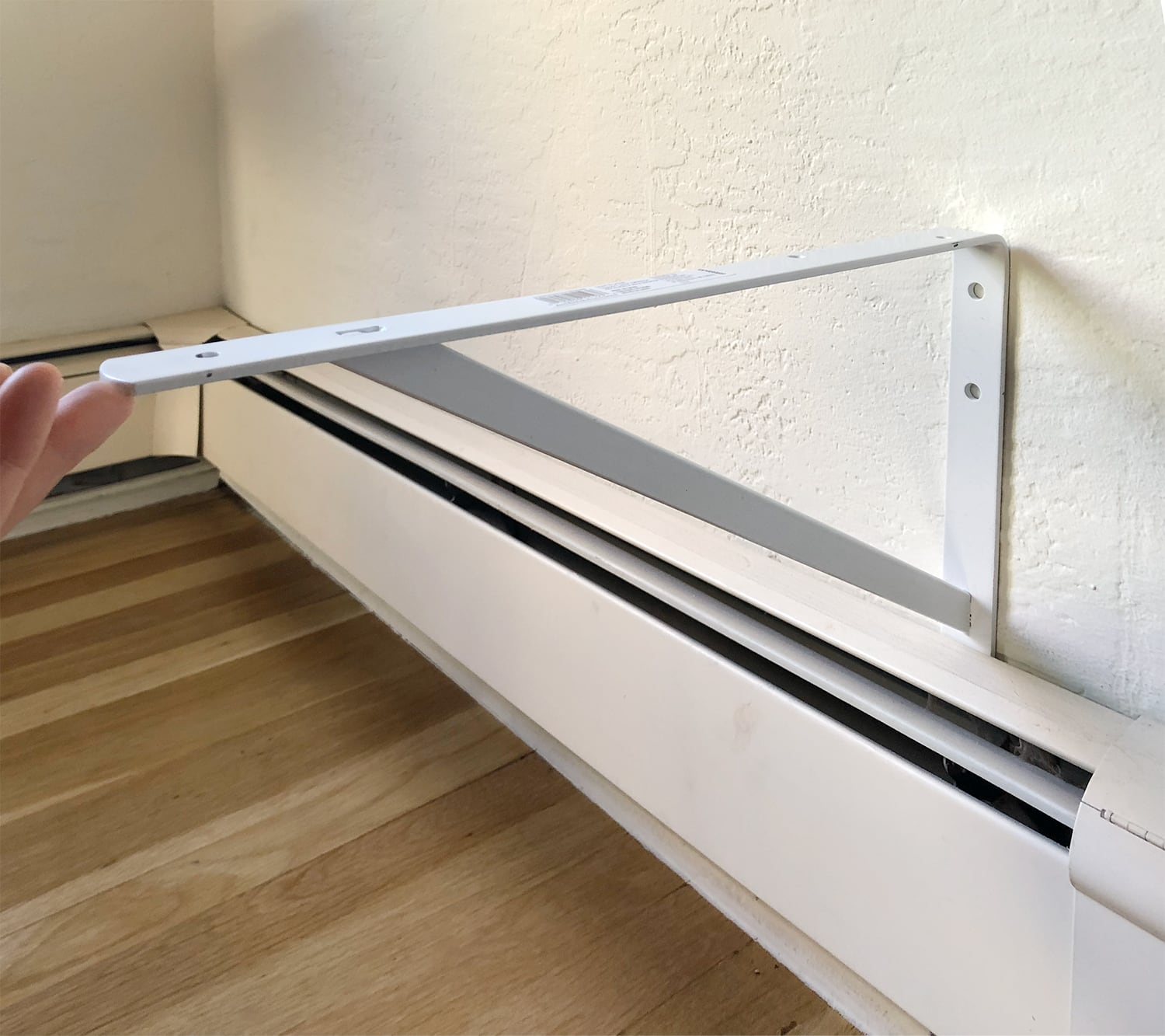 steel bracket above baseboard radiator
